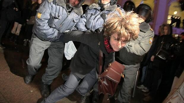 Police officers detain an opposition activist during a protest against vote rigging in St. Petersburg on Monday.