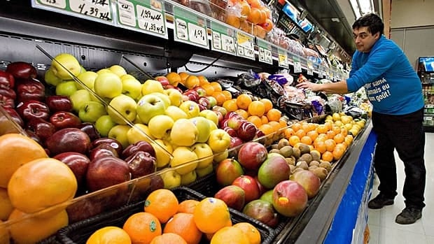 Grocery store owner Gilles Robin works on his fruits and vegetable display on Nov. 28 2006 in Breakeyville, Que. Food prices have consistently risen over the years, but the proportion of household spending Canadians devote to food has fallen.