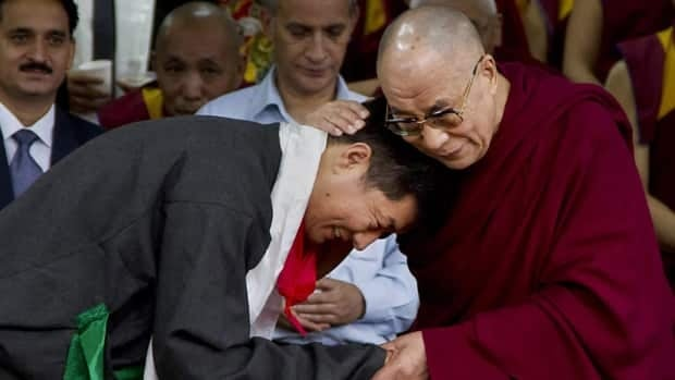 Lobsang Sangay, left, the new prime minister of Tibet's government in exile, is blessed by Tibetan spiritual leader the Dalai Lama during his swearing-in ceremony at the Tsuglakhang Temple in Dharmsala, India.