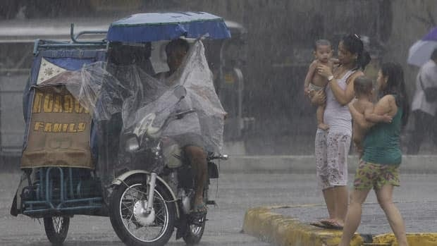 Filipino women carry their babies under the rain as they cross a street in suburban Manila on Tuesday. Tropical storm Nock-ten, locally named Juaning, has entered the country, causing suspension of classes up to the high-school level in some parts of the country, including the capital.