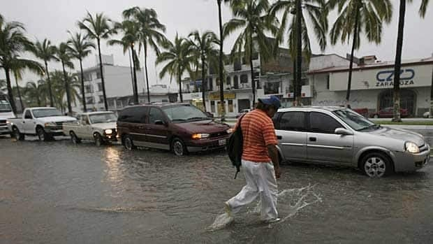 A pedestrian walks on a flooded street on Monday in Puerto Vallarta, Mexico.