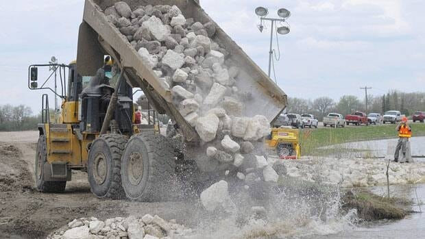 Rocks were dumped into a gap at the Hoop and Holler Bend Friday to seal the dike and stop the intentional flooding land in southern Manitoba.