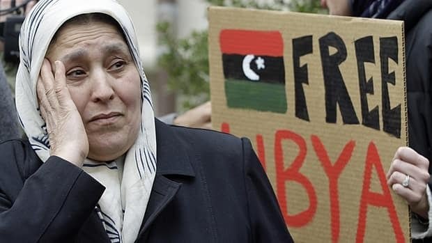 Libyan-American protesters gather Friday at the Libyan ambassador's residence in Washington, where they raised a pre-Gadhafi era Libyan flag.