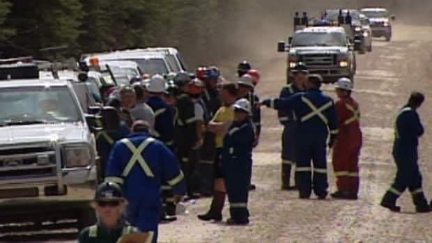 Workers cleaning up an oil spill in northern Alberta assemble while Plains Midstream searches for the source of a employee distress call Wednesday morning.