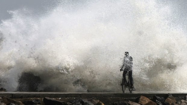 A cyclist makes his way past waves breaking on the Bay of Bengal coast in Chennai, India, Wednesday, Dec. 28, 2011, as Tropical Cyclone Thane moved westward toward southern India.