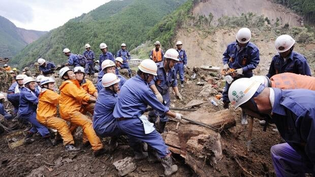 Rescue workers search for missing people Monday among the debris in Gojo, Nara Prefecture, after a powerful storm lashed parts of Japan.