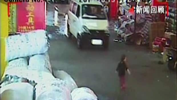 In this image taken from Oct. 13, 2011, security camera video, a two-year-old girl, identified as Wang Yue, is seen just before she is hit by a white van in Foshan in southern China's Guangdong province.