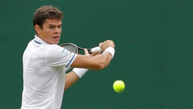 Canada's Milos Raonic plays a return shot to Tunisia's Marc Gicquel at Wimbledon on June 20.