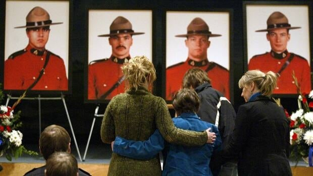 Residents of Mayerthorpe, Alta. embrace during a candlelight service March 3, 2006 one year after RCMP Constables, left to right, Anthony Gordon, Leo Johnston, Brock Myrol and Peter Schiemann were gunned down following a raid on a marijuana grow-op.