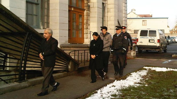 Mohammad Shafia, his wife, Tooba Mohammad Yahya, and their son, Hamed Mohammed Shafia, are escorted by police officers into the Frontenac County Court courthouse Thursday morning in Kingston, Ont.
