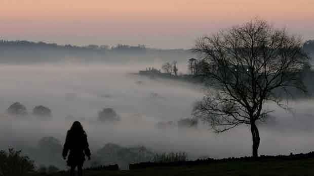 A girl looks out over the fog-covered Leicestershire countryside in England. MS cases are more common at higher latitudes in temperate climes.