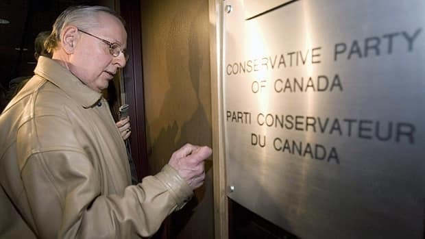 Andre Thouin, an official with Elections Canada, knocks on the door of Conservative Party of Canada headquarters in Ottawa on April 15, 2008, during an RCMP raid of the office. (Tom Hanson/Canadian Press)
