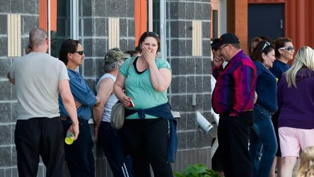 Residents of Slave Lake, Alta. are seen outside the Athabasca evacuation centre on May 19, in the wake of wildfires that have ravaged the town in recent weeks.