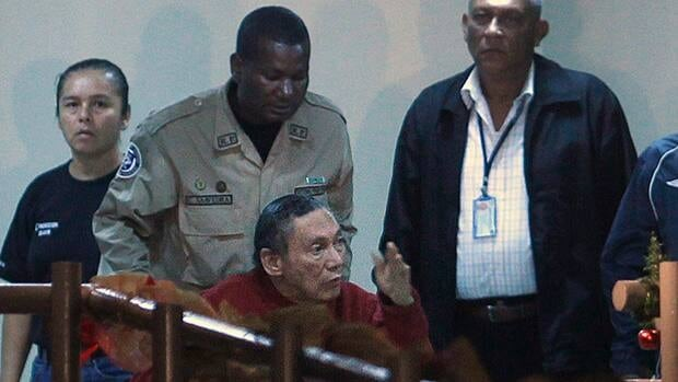 Manuel Noriega, left, gestures while being carried in a wheelchair by police officers inside El Renacer prison in the outskirts of Panama City, on Sunday.