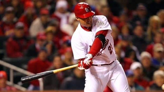 Allen Craig of the St. Louis Cardinals hits an RBI single in the bottom of the sixth inning during Game 1 of the MLB World Series against the Texas Rangers at Busch Stadium in St Louis.