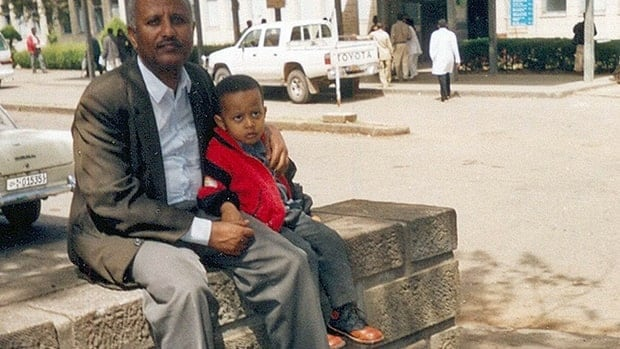 In this 2002 photo, Wondu Bekele sits with his son Mathiwos outside the the Black Lion Hospital in Addis Ababa, Ethiopia.  Mathiwos died eight months later in September 2003 at the age of four because the hospital had no ward to keep vulnerable cancer patients separate from other patients.