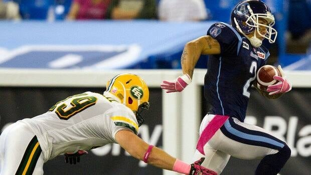 Toronto Argonauts kick returner Chad Owens, right, breaks a tackle by Edmonton Eskimos linebacker Mike Cornell during first half CFL action in Toronto on Friday.