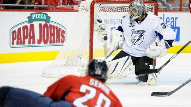 Goalie Dwayne Roloson, right, of the Tampa Bay Lightning makes a save as Alexander Semin of the Washington Capitals watches his shot go off the post.