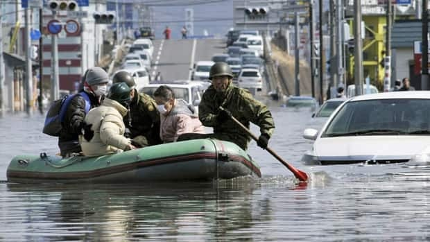 Members of Japan's self-defence forces rescue people stranded at a flooded city centre in Ishinomaki, northern Japan, in March, two days after a powerful earthquake-triggered tsunami hit the country's east coast.