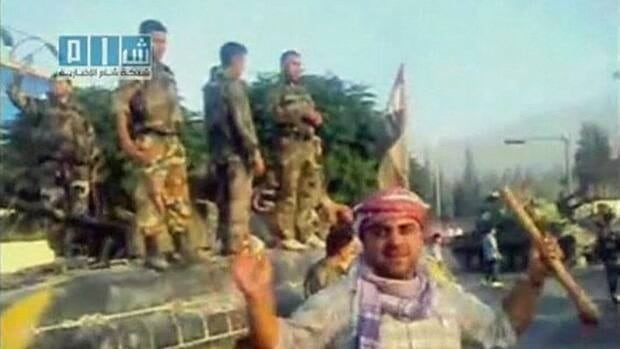 Army defectors stand atop a tank as a resident gestures in Hama in this still image taken from video posted on YouTube July 31, 2011. The content of the video could not be independently verified.