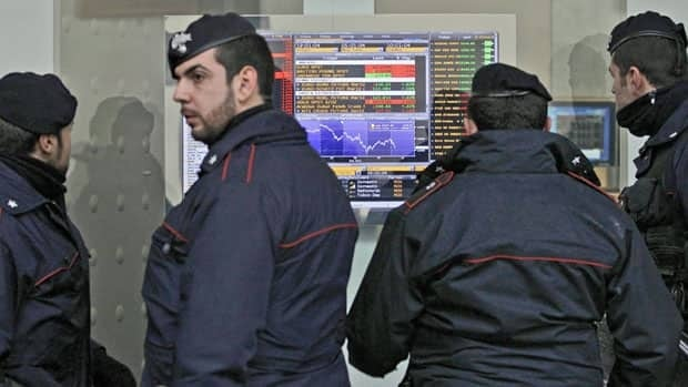 Italian paramilitary police watch a monitor showing financial market data in Milan Monday. Italian and Spanish bond yields rose again as Moody's warned about a possible downgrade of all EU members.