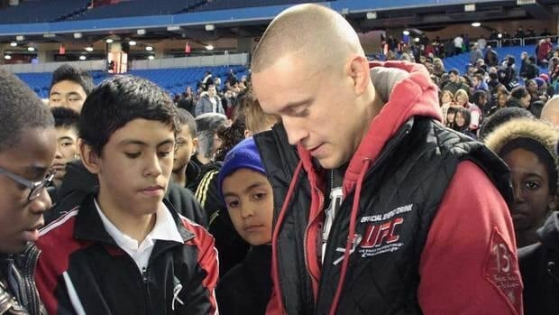 UFC featherweight Mark Hominick, of Thamesford, Ont., signs autographs after delivering an anti-bullying message to young fans at the Roger's Centre in Toronto Tuesday afternoon.