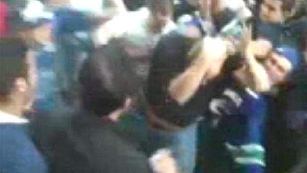 Robert McKay covers his head as rioters swarm him June 15.