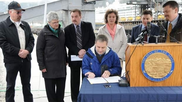 Whitehorse Mayor Bev Buckway, second from left, and other officials watch as Alaska Gov. Sean Parnell, seated, signs House Bill 119 into law Friday at the Skagway Ore Terminal in Skagway, Alaska.