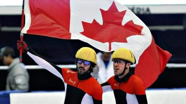 Canada's Charles Hamelin, left, celebrates his gold-medal win with teammate and silver medallist Michael Gilday in the men's 1000-metres Sunday in Saguenay, Que.