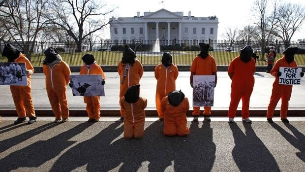 Protesters seeking the closure of the Guantanamo Bay detention facility demonstrate outside the White House in January. The U.S. will resume military trials at the naval base. (Jim Young/Reuters)