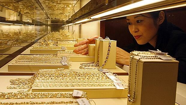 An employee arranges gold necklaces on display in Tokyo. Investors have flocked toward gold as the U.S. dollar falters of late.