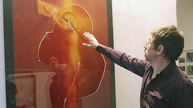 Museum curator Jean-Marc Ferrari shows the damage U.S. artist Andres Serrano's artwork Immersion (Piss Christ) suffered in Sunday's attack at Avignon's Lambert Collection Museum of Contemporary Art.