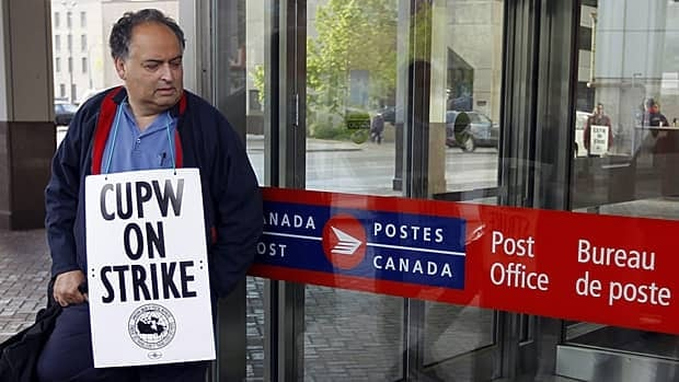 A Canadian Union of Postal Workers member pickets in front of the main post office in Winnipeg on Friday, the first day of a Canada Post strike.