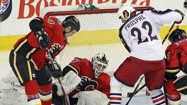 Jay Bouwmeester, left, and goaltender Miikka Kiprusoff, centre, of the Calgary Flames defend the net against Blue Jackets forward Vaclav Prospal on Thursday night.
