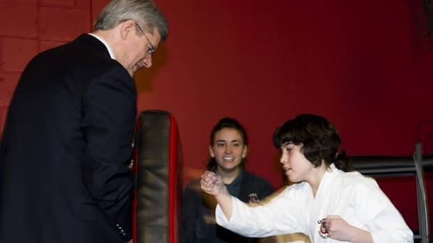 Prime Minister Stephen Harper, left, takes part in a martial arts exercise with Michaela Capuano at a fitness gym in Ottawa on Sunday.