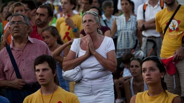 Pilgrims pray at the street during a mass at the Cibeles square on Tuesday ahead of the four-day visit of Pope Benedict XVI in Madrid starting Thursday.
