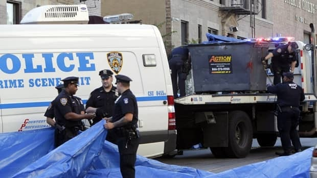 Police officers prepare to remove a dumpster that is believed to have contained the remains of a missing eight-year old boy in the Brooklyn borough of New York.