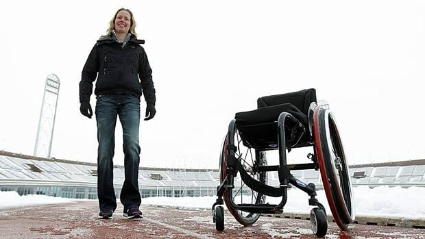 Monique van der Vorst poses in front of her wheelchair at the Olympic stadium in Amsterdam.
