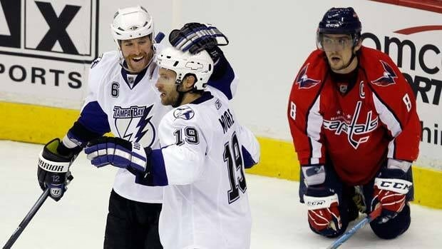 Tampa Bay Lightning left wing Ryan Malone (left) and Dominic Moore celebrate in front of Washington Capitals captain Alex Ovechkin during Game 1.