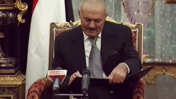 Yemen's longtime leader Abdullah Saleh signs a document agreeing to step down in Riyadh, Saudi Arabia, on Wednesday.