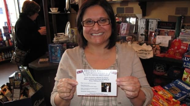 British pantry owner Hamida Rashid holds a tea party invite.