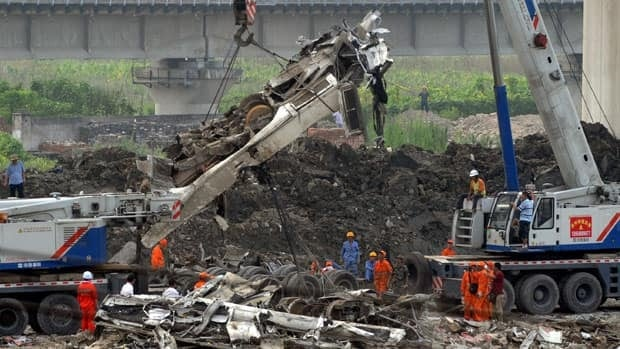 The wreckage of a carriage is lifted up for transportation at the train crash site near Wenzhou, east China's Zhejiang Province, on Tuesday. State media reports that design flaws and human error are behind the weekend crash that killed 39 people.