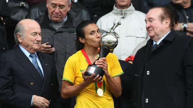 Marta kisses the trophy after Brazil defeated Chile to win the Women's South American Championship last year as FIFA President Joseph Blatter, left, looks on.