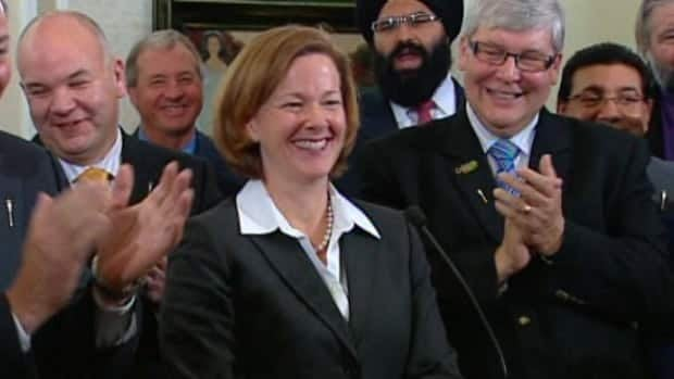 Alberta Premier Alison Redford is applauded by members of her new cabinet at a news conference Wednesday.