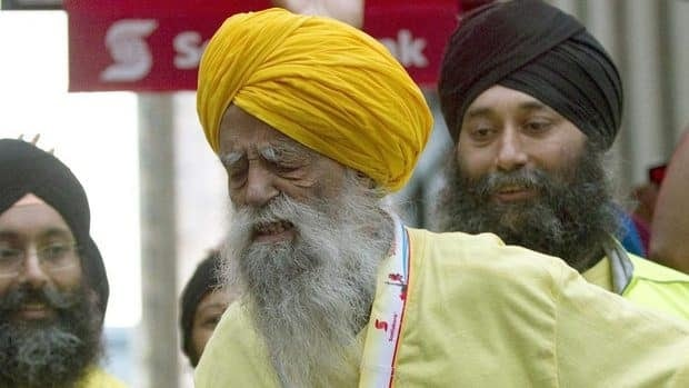 Fauja Singh grimaces as he crosses the finish line Sunday in the Scotiabank Toronto Waterfront Marathon.