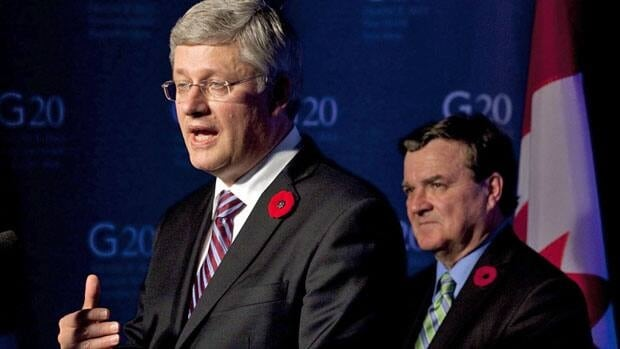 Minister of Finance Jim Flaherty listens as Prime Minister Stephen Harper responds to a question during a closing news conference at the G20 Summit in Cannes, Nov. 4, 2011. The Canadian Federation of Independent Business is asking the government to delay a planned increase in employment insurance premiums.