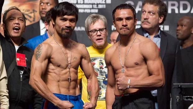 Manny Pacquiao, left, of the Philippines, and Juan Manuel Marquez, of Mexico, pose for photos during an official weigh-in ceremony in Las Vegas on Friday. Pacquiao is scheduled to defend his WBO welterweight title against Marquez on Saturday.