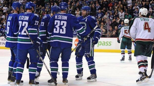 Ryan Kesler, right, of the Vancouver Canucks celebrates with teammates after a goal during Vancouver's overtime win against the Minnesota Wild on Saturday evening.