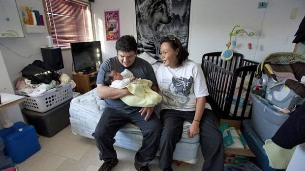 Stella Wheesk and her husband Harold Wesley hold one-month-old Rain Wesley in their one room home in a dorm styled temporary housing trailer in Attawapiskat, Ont., on Tuesday. The federal government placed the reserve under third-party management on Wednedsay.