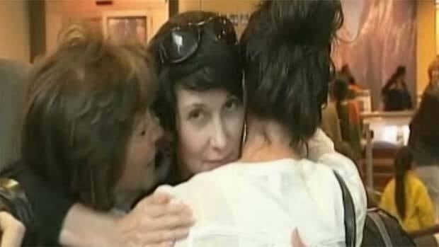 Dorothy Parvaz, centre, is greeted by family members at Vancouver airport Thursday.